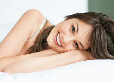 Buy stock photo Happy young lady resting on a bed with a smile - closeup portrait