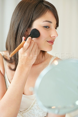 Buy stock photo Makeup - Young female applying makeup on her face