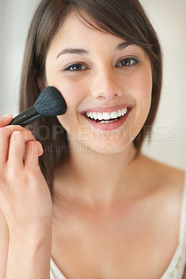 Buy stock photo An attractive young lady applying blusher
