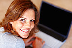 Happy young woman with a laptop at home