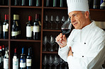 Male chef tasting red wine