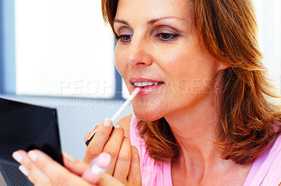 Buy stock photo Beautiful young woman applying cosmetics on her li