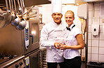 Smiling male chef with female trainee