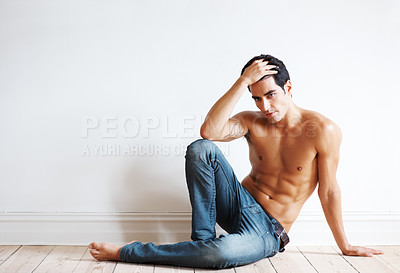 Buy stock photo Portrait of a muscular young male model posing  on a floor against a white wall with lots of copyspace