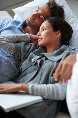 Buy stock photo Young romantic couple relaxing while looking away
