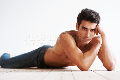 Buy stock photo Portrait of a muscular young man thinking while lying on the floor