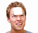 Young man balancing white blank card on forehead