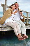 Romantic old couple sitting on jetty by sea