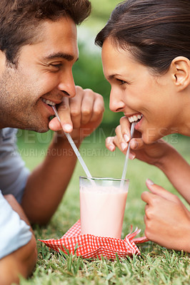 Buy stock photo Romantic couple enjoying a milkshake
