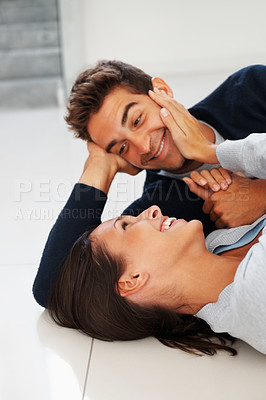 Buy stock photo Attractive couple lying on the floor laughing