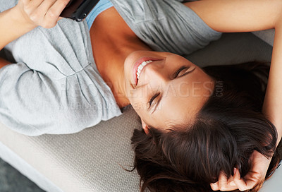 Buy stock photo Smiling woman looking at smart phone