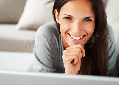 Buy stock photo Pretty woman lying on sofa with chin in hand
