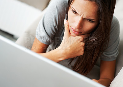 Buy stock photo Pretty woman deep in thought while looking at laptop