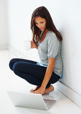 Buy stock photo Pretty woman working on laptop and holding coffee
