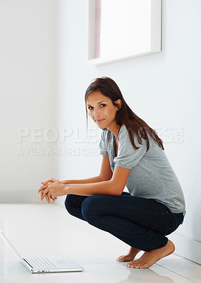 Buy stock photo Pretty woman crouched in front of laptop