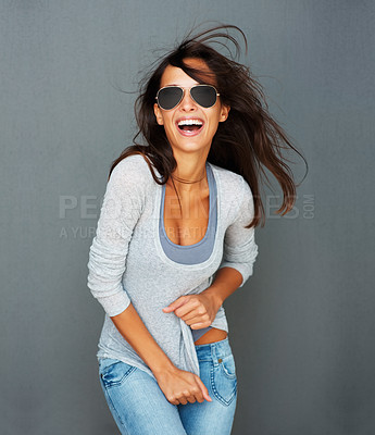 Buy stock photo Sexy woman wearing sunglasses against a gray background