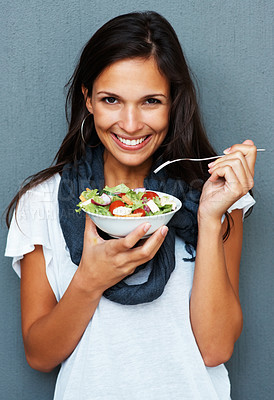 Buy stock photo Woman smiling while holding a bowl of salad against blue background