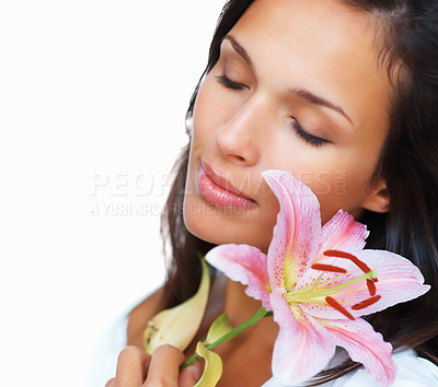 Buy stock photo Portrait of a beautiful woman holding a stargazer lily against cheek with her eyes closed, isolated on white - copyspace