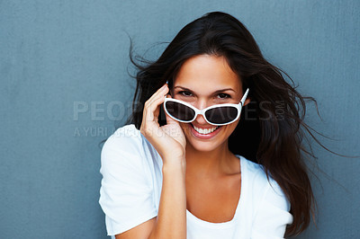 Buy stock photo Pretty woman holding sunglasses on tip of her nose