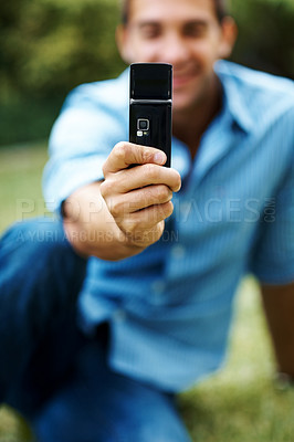 Buy stock photo Closeup shot of a man taking a photo with a cellphone in the park
