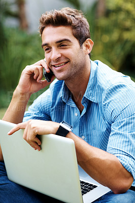 Buy stock photo Shot of a handsome young man talking on mobile phone while working on laptop