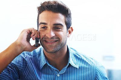 Buy stock photo Shot of a happy young man speaking on a mobile phone