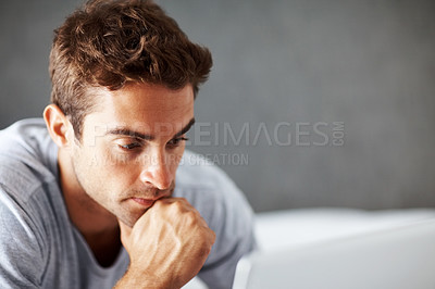 Buy stock photo Shot of a young man working on laptop while lying on a bed at home