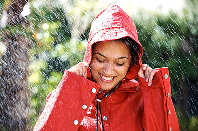 Buy stock photo Portrait of a pretty young woman holding a red raincoat hat on head - Outdoors