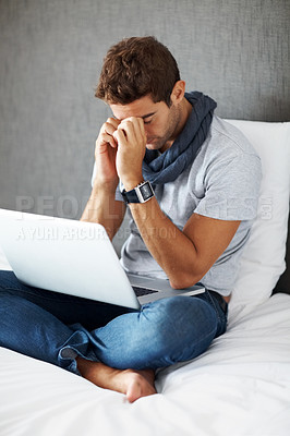 Buy stock photo Portrait of a thoughtful young man using laptop while sitting on bed