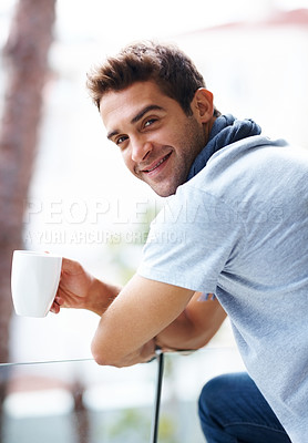 Buy stock photo Portrait of a happy young man having a cup of coffee on his balcony in the evening