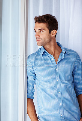 Buy stock photo Shot of a handsome young man looking away and thinking