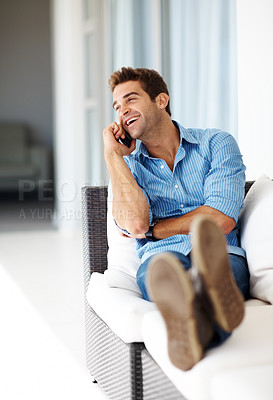 Buy stock photo Shot of a relaxed young guy enjoying conversation on cellphone at home