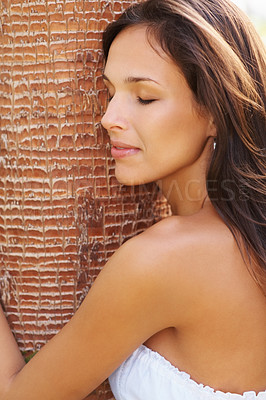 Buy stock photo Pretty brunette hugging a tree with eyes closed