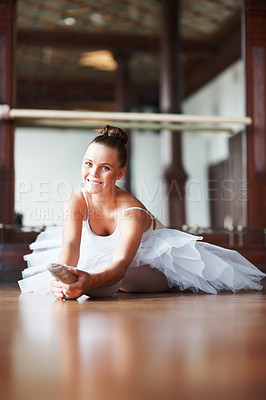 Buy stock photo Portrait of a smiling young ballet dancer stretching on dance floor