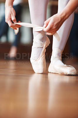 Buy stock photo Closeup portrait of a ballerina putting her shoes on with a blurred man practicing in background