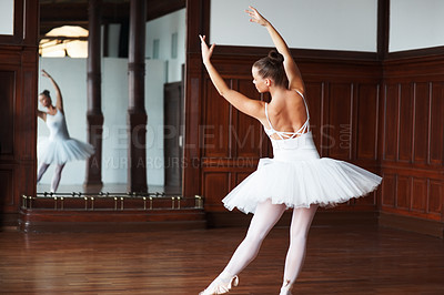 Buy stock photo Rear view of a ballerina wearing white tutu dancing in front of a mirror