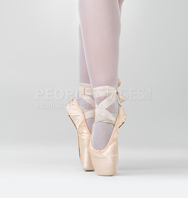 Buy stock photo Low angle view of a dancer in ballet shoes dancing in Pointe against white - copyspace