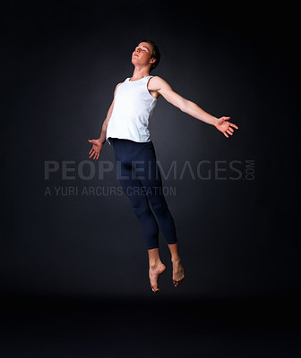 Buy stock photo Full length of a young graceful male ballet dancer performing against black background
