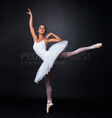 Buy stock photo Full length of a pretty young ballerina performing against black background