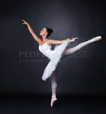 Buy stock photo Full length of a young ballerina dancing gracefully against black background