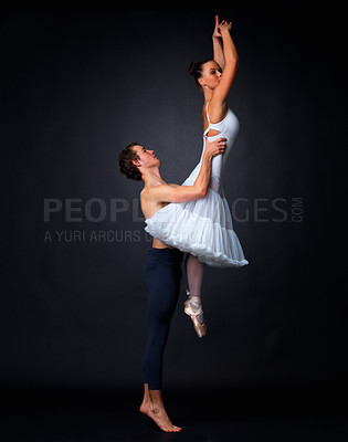 Buy stock photo Side view of a male ballet dancer lifting ballerina against black background