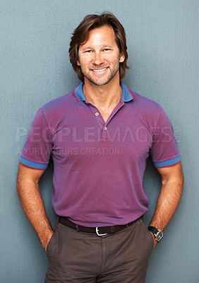 Buy stock photo Portrait of a happy smart mature man smiling against colored background, hands in pockets