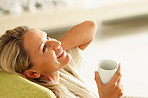Smiling middle aged woman with a cup of tea or coffee looking up