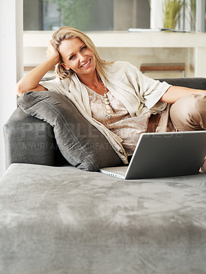 Buy stock photo Portrait of a smiling pretty female lying on sofa while using laptop