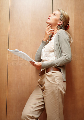 Buy stock photo Thoughtful mature woman looking up while reading a document against wooden background