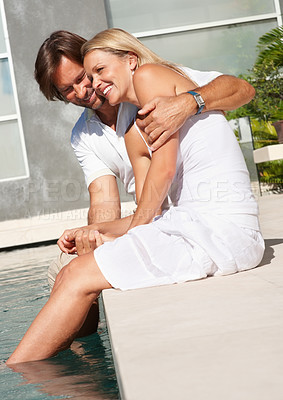 Buy stock photo Romantic mature man and woman sitting by the swimming pool on a sunny day