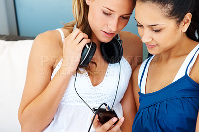 Buy stock photo Portrait of two young female friends listening to music on mobile phone