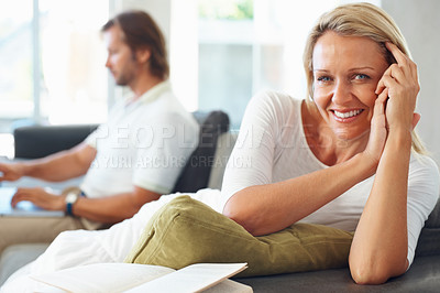 Buy stock photo Portrait of a relaxed mature woman with man using laptop in the background at home