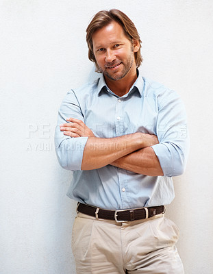 Buy stock photo Portrait of a smart mature man smiling with hands folded against white background