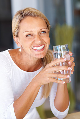 Buy stock photo Closeup portrait of a happy mature woman holding a glass of water